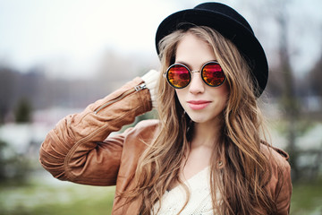 Young happy woman with long brown hair in sunglasses and black hat, portrait