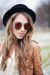 Cute smiling woman fashion model with long brown hair in sunglasses and black hat, portrait