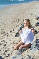 Attractive woman in bikini hiding behind a big hat on the beach