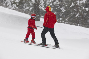 Child learning how to ski with instructor. Winter sport