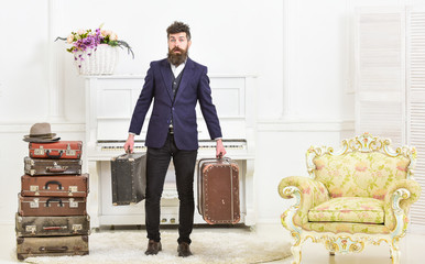Macho attractive, elegant on surprised face carries vintage suitcases. Man with beard and mustache wearing classic suit delivers luggage, luxury white interior background. Butler and service concept.