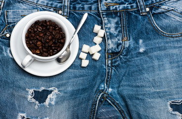 Cup with coffee beans, spoon and refined sugar lay on jeans near zip, denim background. Fresh brewed coffee concept. Mug full of coffee beans on jeans, top view