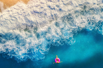 Aerial view of woman swimming on the pink swim ring in the sea in the morning in Europe. Summer landscape with girl, beach, blue water, beautiful waves at sunrise. Top view. Travel and holiday. Resort
