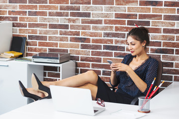 Relaxed business woman with legs on the desk texting on phone