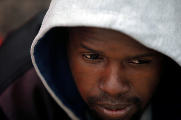 A migrant rests after arriving on a rescue boat at the port of Tarifa