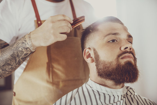 Man in the process of trimming a beard in a barbershop. Photo in vintage style