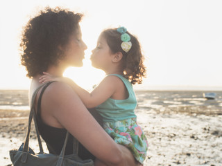mother and daughter kissing at sunset on the beach
