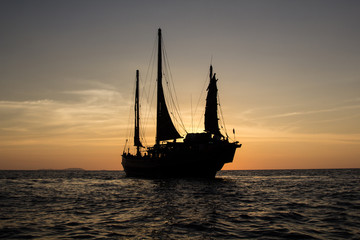 Old junk style sailboat cruising in the sunset in the Andaman sea in Thailand