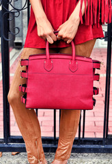 Fashionable woman on the street. City lifestyle. Female fashion.Stylish boho traveler woman wearing suede brown pants red blouse with fringe holding red leather bag.