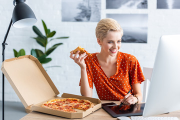 happy female freelancer eating pizza and drawing on graphic tablet at home office