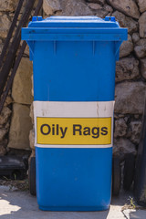 c72c9865f052ce Blue bin with a sign on it for oily rags.