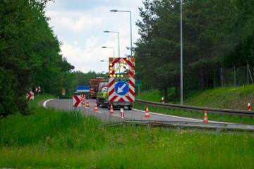 A warning sign on the road runs ahead. Road sign. Road repair