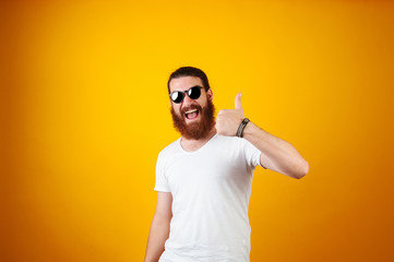 Hipster bearded man showing thumb up. He is wearing sunglasses and a white shirt on a yellow background.