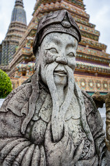 Traditional Thai stone buddha sculpture with pagone in the background in a Thai temple, Wat Pho, Bangkok, Thailand