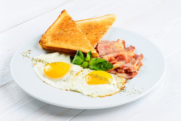 Tasty English breakfast with fried eggs, bacon and toasts on the
