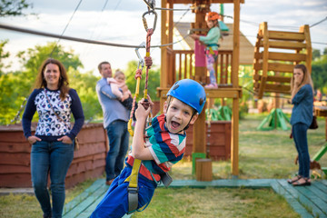 Adorable little boy enjoying his time in a rope playground structure at adventure park,