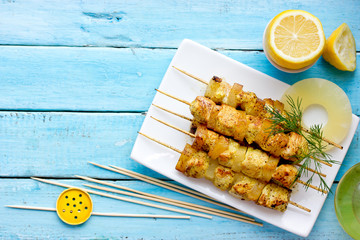 Hawaiian skewers with chicken and pineapple slices on plate top view