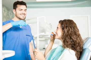 Dentist Showing Technique Of Brushing Teeth To Patient In Clinic