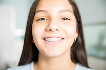 Smiling Teenage Girl Wearing Braces At Dental Clinic