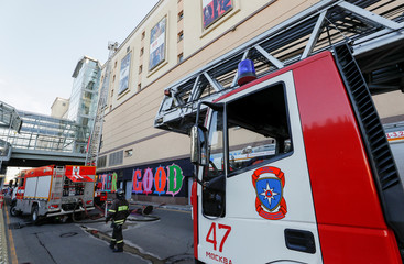 A view shows fire trucks in front of a shopping mall as it was evacuated after a fire broke out in Moscow