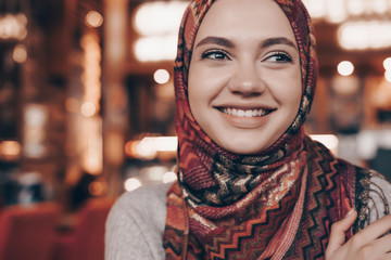 beautiful smiling Muslim girl with headscarf sitting in restaurant and waiting for her food