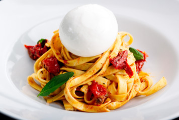 Tasty fettuccine with meat and goat cheese