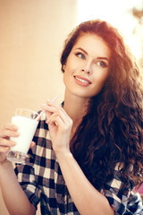 Beautiful attractive fashionable woman with curly hair drinks a milkshake in the summer in the city
