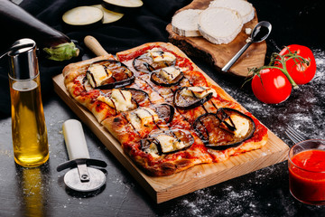 Bright pizza with vegetables on wooden board