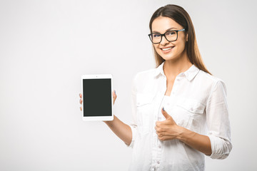 Friendly smiling beautiful young woman presenting your product on tablet computer. Business concept on white background.