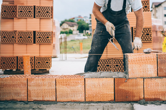 industrial construction site details with worker laying bricks