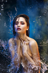 Beautiful sensual topless brunette girl surrounded with sparkling  water splashes and drops covers her breast with her hands in theatrical smoke. Conceptual art photo