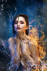 Beautiful topless brunette girl surrounded with sparkling  water splashes and fire flames on her naked shoulder covers her breast with her hands an in theatrical smoke. Concept art