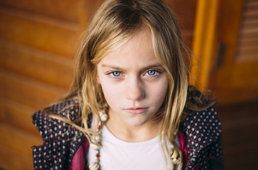 Close-up of girl's blue eye posing in wooden background