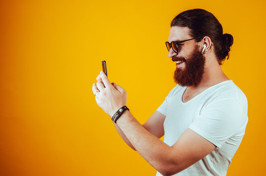 Cheerful man taking a photo and listening to music. Browsing the internet.