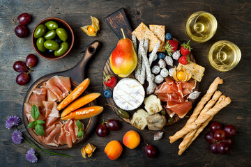 Appetizers table with italian antipasti snacks and wine in glasses. Cheese and charcuterie variety board over rustic wooden background