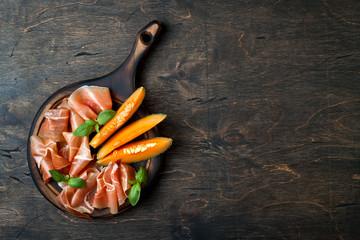 Jamon serrano or prosciutto with melon over rustic wooden background. Italian or spanish antipasti, appetizer board