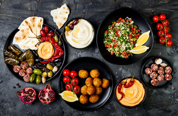 Poster Klaar gerecht Arabic traditional cuisine. Middle Eastern meze platter with pita, olives, hummus, stuffed dolma, labneh cheese balls in spices. Mediterranean appetizer party idea