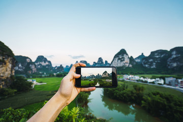 Hand taking photo of Guangxi province landscape