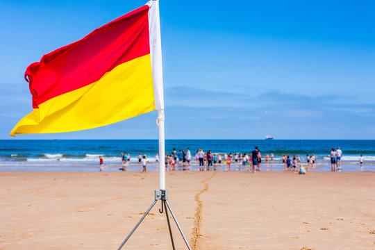 A red and yellow lifeguard safety flag on a beach with families and children in the background playing in the sea