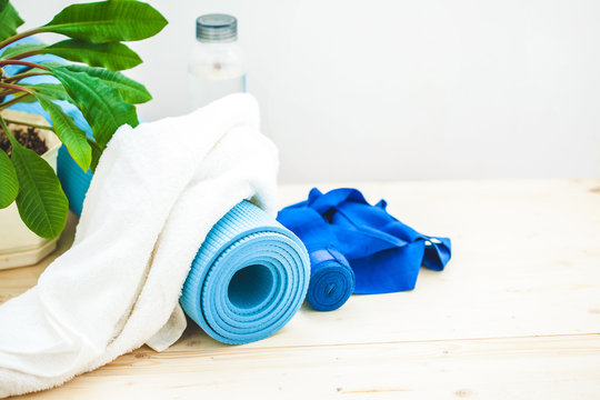 set for sports, a yoga mat, a towel and a bottle of water on a light background. The concept of a healthy lifestyle Place for text