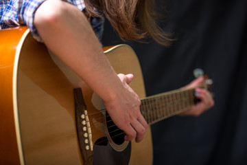 Girl playing an acoustic guitar on a dark background in the Studio. Concert young musicians