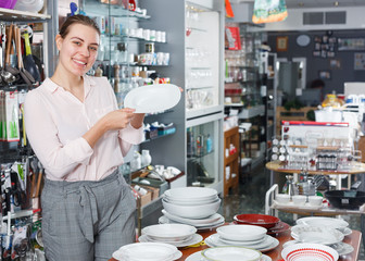 Young woman consumer ceramic plates  in tableware shop
