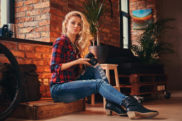 Sensual blonde hipster girl with long curly hair dressed in a fleece shirt and jeans holds a camera sitting on a wooden box at a studio with loft interior.