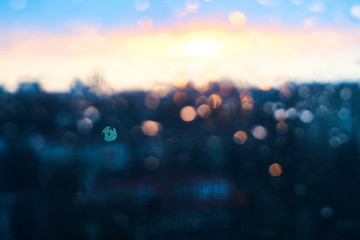 Rain drops texture on window glass with stunning vintage blue violet sunset light abstract blurred cityscape skyline bokeh background. Soft focus. Fotomurales
