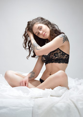 Beautiful woman with tattoo in  lace   underwear  on the bed.