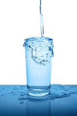 overflowing mineral water in transparent glass with drops and bubbles isolated over white, blue background, close up