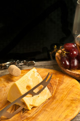 Top view, medium distance of a wedge of cheese with a cheese knife cutting on a rare, wood plate with a round, wood bowl of freshly picked red grapes  and a corkscrew and cork, wine tasting event