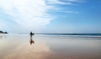 Surfer with surfboard walks on coast line