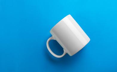 Flipped white mug on blue background
