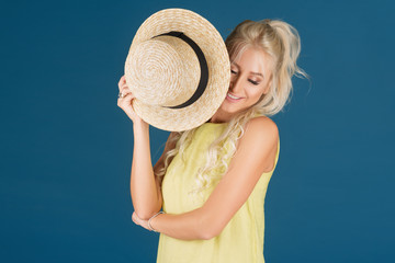 A slender blonde girl in a short yellow dress and a straw hat on her head stands on a blue background in the studio. Hides his face from the sun on the beach